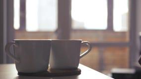 Zwei Schalen heißer Tee stehen auf dem Tisch, ein Mann, ` s, das Hand ein Getränk nimmt stock video