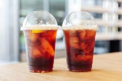 Zwei Schalen Iced kalter Gebräunitrokaffee mit Zitrone auf Holztisch mit Unschärfehintergrund lizenzfreie stockbilder