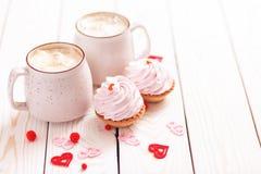 Zwei Schalen Kaffee und rosa Sahnekleine kuchen auf weißem hölzernem Hintergrund Konzept-Valentinstag, Geburtstag, Hochzeitstag stockfoto