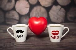 Zwei Schalen mit einem heißen Getränk von Liebhabern zwischen ihnen ein rotes Herz Lizenzfreie Stockfotografie