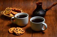 Zwei Schalen schwarzer Kaffee mit amerikanischen Plätzchen und einer türkischen Kaffeemaschine des Lehms auf dunkelbraunem hölzer stockfotos