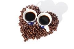 Zwei Schalen schwarzer Kaffee und Herz gemacht von den Kaffeebohnen auf wei?es backgroung lokalisierter Draufsicht stockfotos