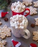 Zwei Schalen und Eibische der heißen Schokolade, gegen grauen Hintergrund u. Weihnachtszusammensetzung mit Schneeflockenlebkuchen lizenzfreies stockfoto