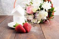 Zwei Schalen und zwei Erdbeeren mögen Herz shap und Blumenstrauß von flo Stockfoto