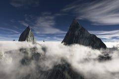 Zwei scharfe Spitzen umgeben durch niedrige hängende Wolken Stockfotos