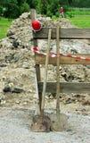 zwei Schaufeln, eine rote Lampe zum Zaun, den Abzugsgraben einschließend begraben im Boden Stockfotografie