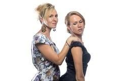 Zwei scherzende Schwestern auf weißem Hintergrund Stockbild
