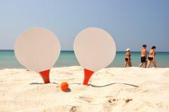 Zwei Schläger und eine Kugel auf dem Strand Stockfotos