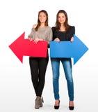 Zwei schöne Frauen, die roten und blauen Pfeil anhalten, verließen und recht Stockfotografie