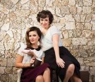 Zwei schöne Freundinnen, die einen Tee trinken Lizenzfreie Stockfotos