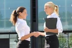 Zwei schöne Geschäftsfrauen, die Hände in der Straße rütteln Stockfotos