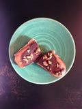 Zwei Schokoladehaselnuß Eclairhälften auf einer grünen Platte Lizenzfreie Stockfotos