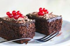 Zwei Schokoladenkuchen mit redberries auf die Oberseite, gedient in einer Platte auf einem Holztisch Stockbild