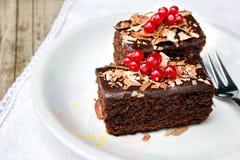 Zwei Schokoladenkuchen mit redberries auf die Oberseite, gedient in einer Platte auf einem Holztisch Lizenzfreie Stockfotos