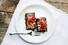Zwei Schokoladenkuchen mit redberries auf die Oberseite, gedient in einer Platte auf einem Holztisch Lizenzfreie Stockbilder