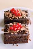 Zwei Schokoladenkuchen mit redberries auf die Oberseite, gedient in einer Platte auf einem Holztisch Lizenzfreies Stockfoto