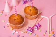 zwei Schokoladenmuffins, eine Geburtstagskerze Partei für Mädchen Kappen und Lametta und mehrfarbige Bonbons auf einem rosa Hinte Lizenzfreie Stockbilder