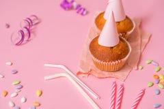 zwei Schokoladenmuffins, eine Geburtstagskerze Partei für Mädchen Kappen und Lametta und mehrfarbige Bonbons auf einem rosa Hinte Lizenzfreie Stockfotografie