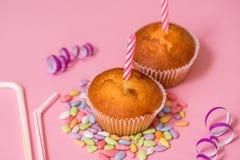 zwei Schokoladenmuffins, eine Geburtstagskerze Partei für Mädchen Kappen und Lametta und mehrfarbige Bonbons auf einem rosa Hinte Lizenzfreies Stockfoto