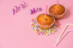 zwei Schokoladenmuffins, eine Geburtstagskerze Partei für Mädchen Kappen und Lametta und mehrfarbige Bonbons auf einem rosa Hinte Stockfotografie