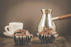 zwei Schokoladenmuffins, Kaffee und Türken/zwei Schokoladenmuffins, -kaffee und -türken auf einem dunklen hölzernen Hintergrund stockfotografie