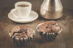 Zwei Schokoladenmuffins, Kaffeetasse und Türken/zwei Schokoladenmuffins, Kaffeetasse und Türken auf einem dunklen hölzernen Hinte stockbilder