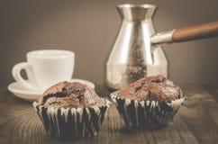 zwei Schokoladenmuffins, weiße Schale und Türken/zwei Schokoladenmuffins, weiße Schale und Türken auf einem hölzernen Hintergrund stockfoto