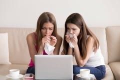 Zwei schreiende Freundinnen beim Aufpassen des traurigen Films Stockfotos