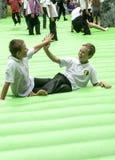 Zwei Schulkinder auf einem inflabable Stonehenge Lizenzfreie Stockbilder