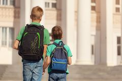 Zwei Schulkinderjungen mit Rucksack am sonnigen Tag Glückliche Kinder gehen zur Schule Rückseitige Ansicht lizenzfreie stockfotografie
