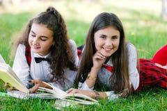Zwei Schulmädchen in den roten Schuluniformen liegen auf einem grünen Rasen mit Büchern stockbild