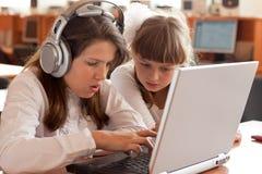 Zwei Schulmädchen führt Aufgabe unter Verwendung des Notizbuches durch stockfotos
