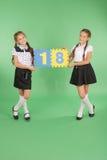 Zwei Schulmädchen halten Farbbrett mit der Nr. achtzehn Stockfotografie
