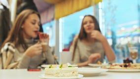 Zwei Schulmädchenfreundinnen, die Cocktails trinken und in einem Caféspaß sprechen Herbst, Winter im Vordergrundkuchen stock video