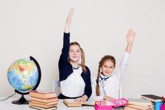 Zwei Schulmädchenmädchen in der Klasse an ihrem Schreibtisch mit zu antworten der Buchhand lizenzfreie stockbilder