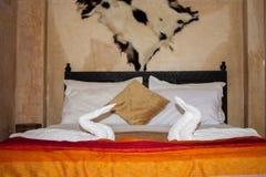Zwei Schwäne gemacht von den Tüchern auf Bett im bunten Raumhotel der Honeymoon-Suite verziert für die Heirat oder gerade die ver lizenzfreies stockbild