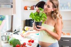 Zwei schwangere beste Freunde, die gesundes Lebensmittel zubereiten Stockfotografie