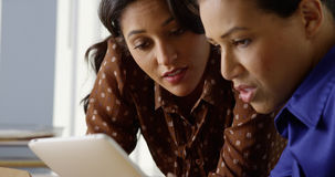 Zwei schwarz und hispanische Geschäftsfrauen, die an Tablet-Computer arbeiten Stockfoto