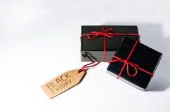 Zwei schwarze eingewickelte Geschenkboxen mit einer roten Schnur und Black Friday-Verkäufen etikettieren auf einer Pappe Lizenzfreie Stockfotografie