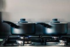 Zwei schwarze glänzende kochende Töpfe auf einem dämpfenden Gasgewindebohrer, wie sie Nahrung nach innen kochen lizenzfreie stockfotos