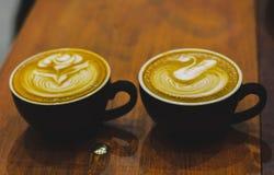 Zwei schwarze Kaffeetassen auf Holztisch Lizenzfreies Stockbild