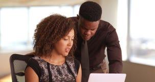 Zwei schwarze millennials, die in einem Highrisebüro arbeiten Lizenzfreie Stockfotos