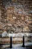Zwei schwarze Pfosten gegen eine strukturierte Wand Stockfotos