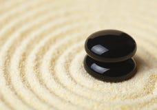 Zwei schwarze Steine setzten sich in einen Stapel auf Sand Lizenzfreies Stockfoto