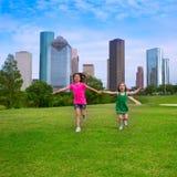 Zwei SchwesterFreundinnen, die Hand in den städtischen Skylinen halten laufen stockbild