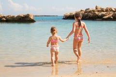 Zwei Schwesterhändchenhalten und Spielen auf dem Strand lizenzfreies stockbild