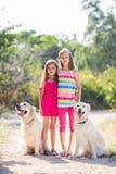 Zwei Schwestern auf einem Weg mit den Hunden im Park Stockfoto