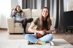 Zwei Schwestern, das jüngere man spielt eine kleine Gitarre in der Front am anderen singt in der Rückseite Stockfotografie