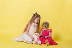 Zwei Schwestern in den Kleidern auf einem gelben Hintergrund und einem mobilen Smartphone lizenzfreie stockfotos
