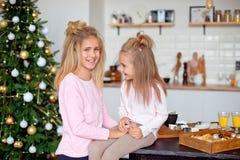 Zwei Schwestern in den Pyjamas im Küchenblick auf einander und Lachen Neues Jahr und Weihnachtskonzept lizenzfreies stockbild